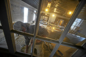 David Washburn paints parts of a window as crews race to finish the Next Stage in Putney last Friday for its reopening celebration.